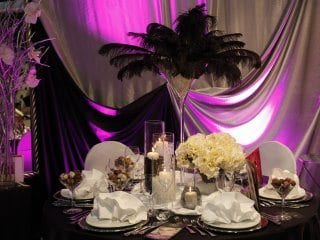Wedding guest table black feather center piece with back uplighting