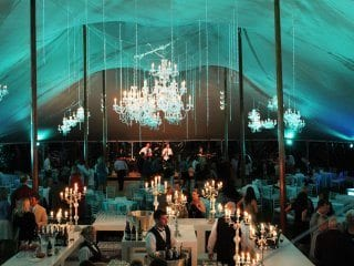 Light blue uplighting in tent for wedding reception