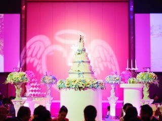 Pin spot on wedding cake with back pink uplighting.