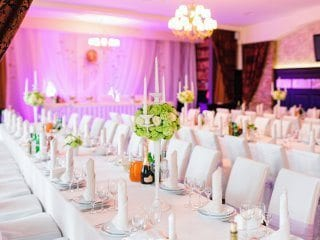Wedding reception guest table with head table and uplighting
