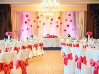 Wedding reception head table with soft uplighting on fabric
