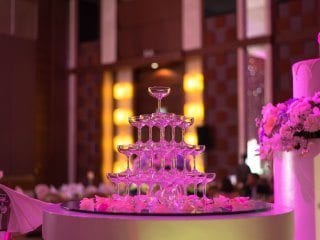 Champagne glass pyramid with pin spot lighting link at wedding reception