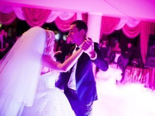 Bride and groom first dance with fog and lighting.  pink
