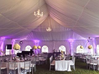 Wedding reception tent  uplighting in daylight soft pink.